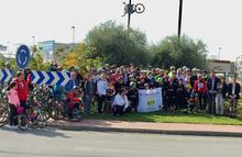 Ciclistas en la rotonda junto a una de las biciletas colocada en una farola